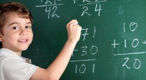 Kid doing math on chalkboard