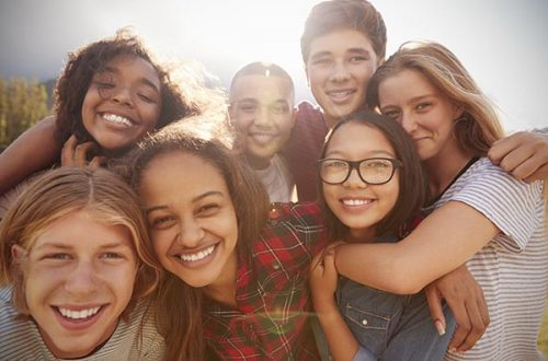 Teenage school friends smiling to camera, close up