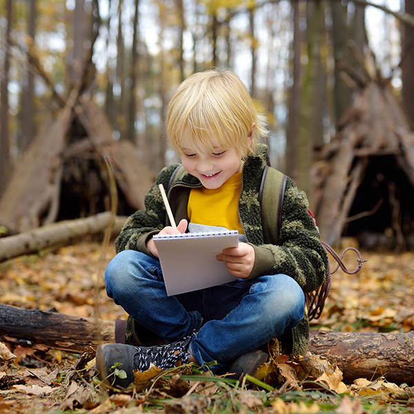 Little boy scout is orienteering in forest. Child is sitting on fallen tree and writing in the notepad. Behind the child is teepee hut.