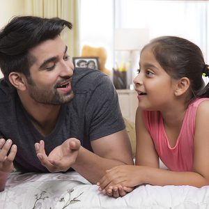 Father and daughter lying on bed and talking