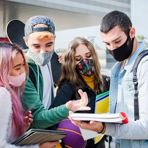 Multiracial students with face mask studying at college campus - New normal lifestyle concept with young students having fun together outdoor